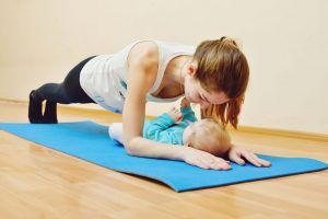 54833837 - young mother does physical yoga exercises together with her baby